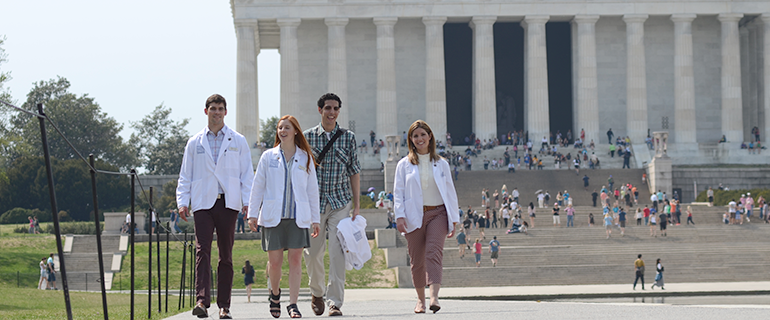 students in lab coats in front of the Lincoln Memorial