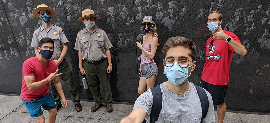 Student wearing a mask, using a selfie stick