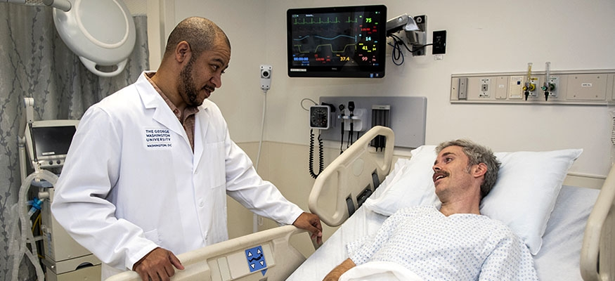 doctor listening to patient in hospital bed with monitor in background