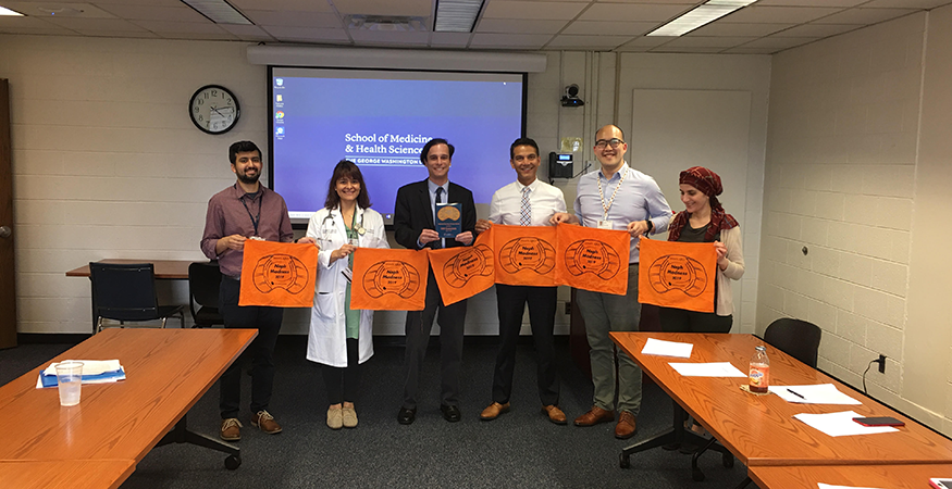 People holding orange banners in a conference room