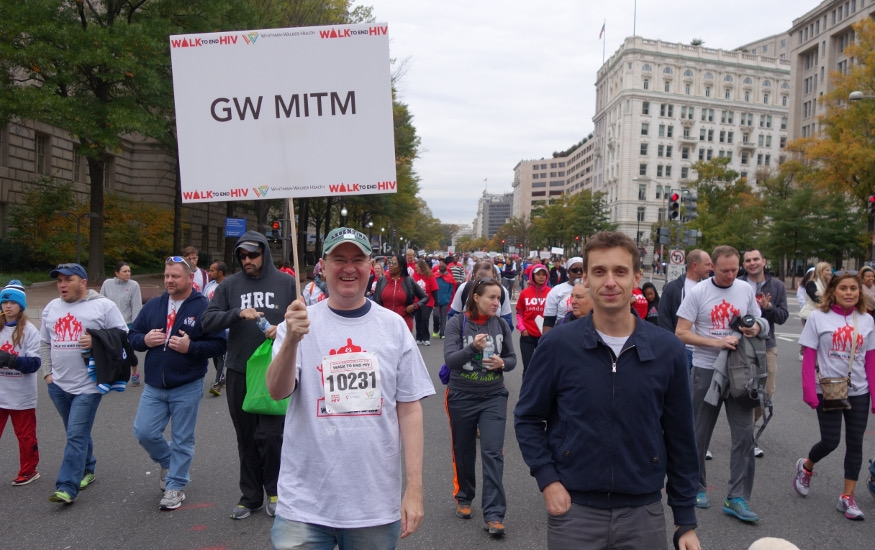 crowd walking and holding signs to end HIV 2015