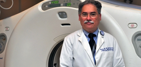 Physician in front of imaging machine