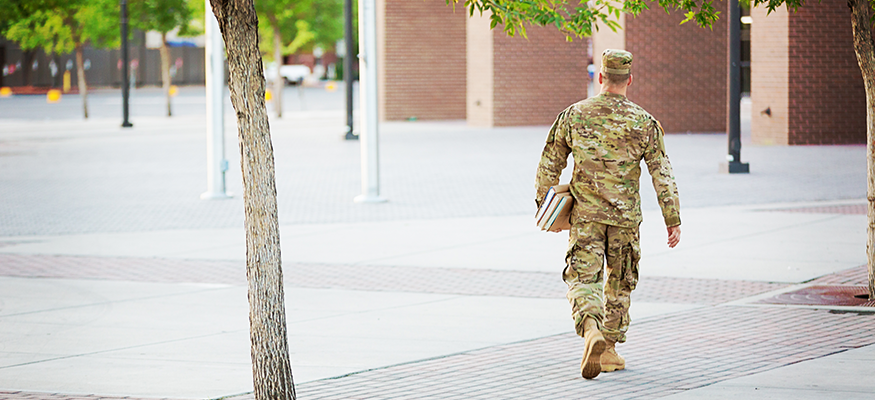 Solider carrying books through quad