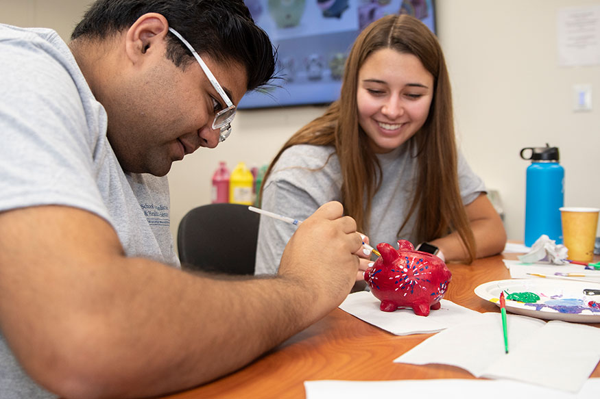Two SMHS students paint a small ceramic piggy bank red