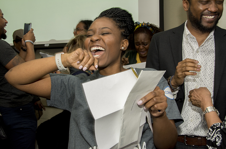 Woman holding white piece of paper laughing