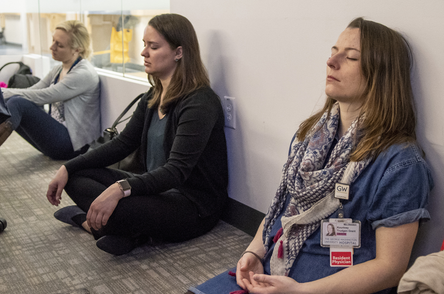 People sitting on the floor with eyes closed meditating