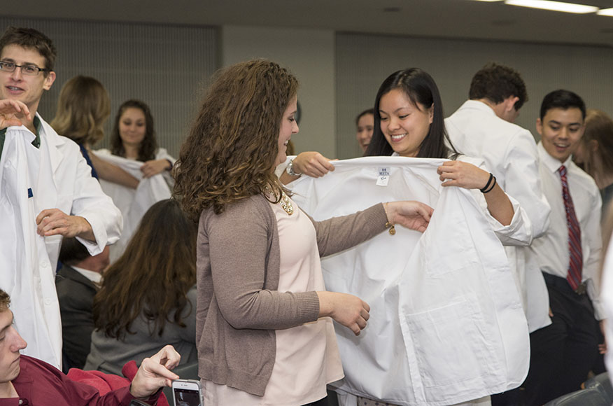One young woman helping another put on a white coat