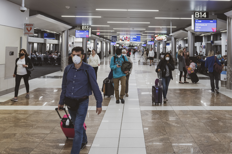 Travelors in the the airport wearing masks.