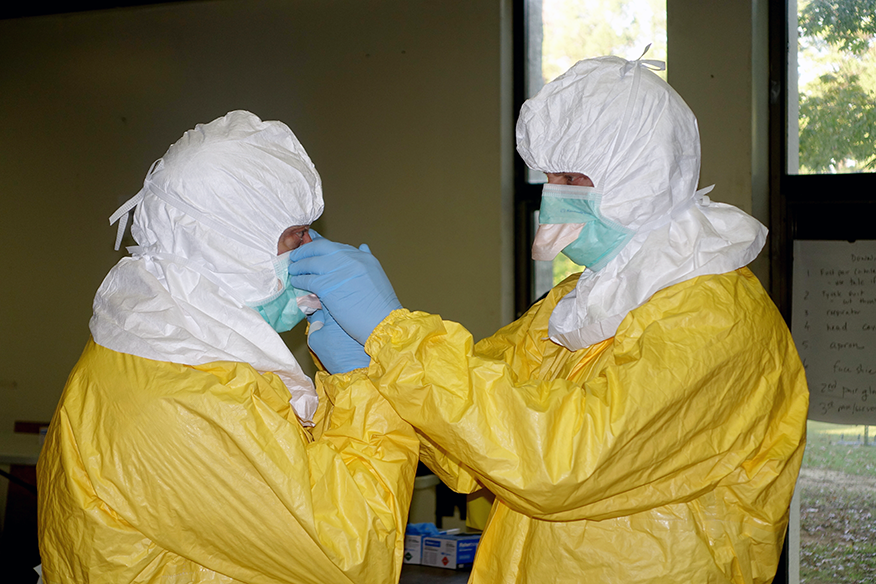 Brian Burt, PA-C '03, B.A. '96, right, helps a fellow volunteer don the Personal Protective Equipment.