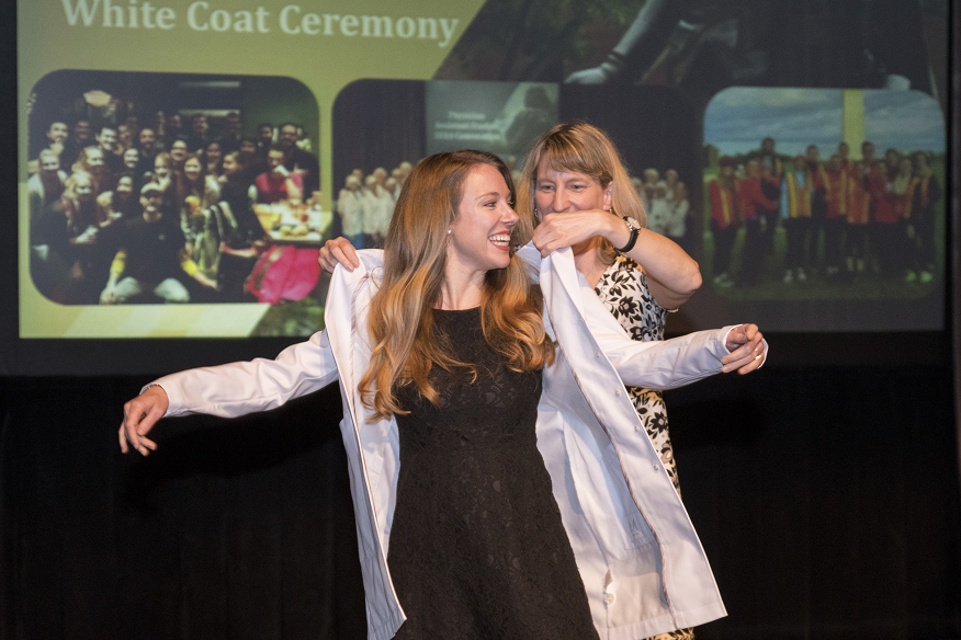A graduating physician assistant student puts on her long white coat with help from a faculty member.
