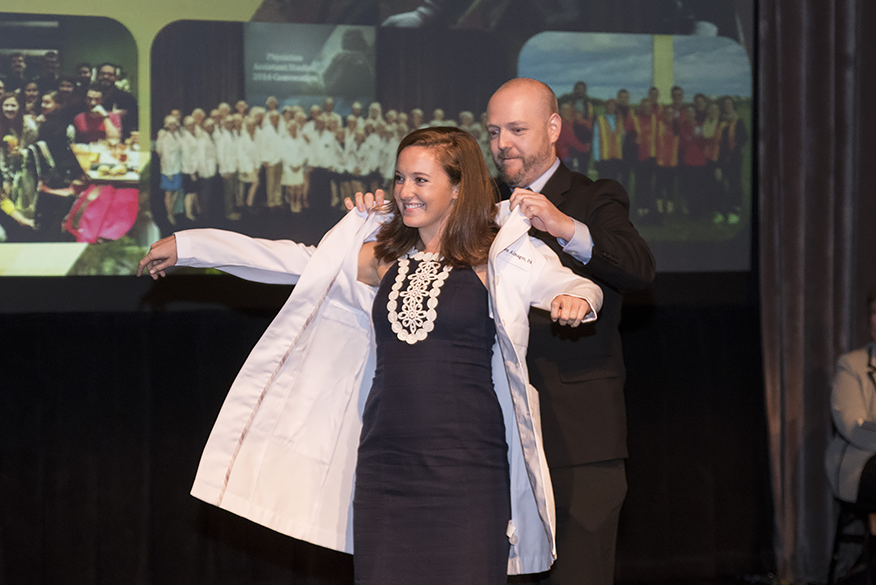 PA graduate receives her long white coat.