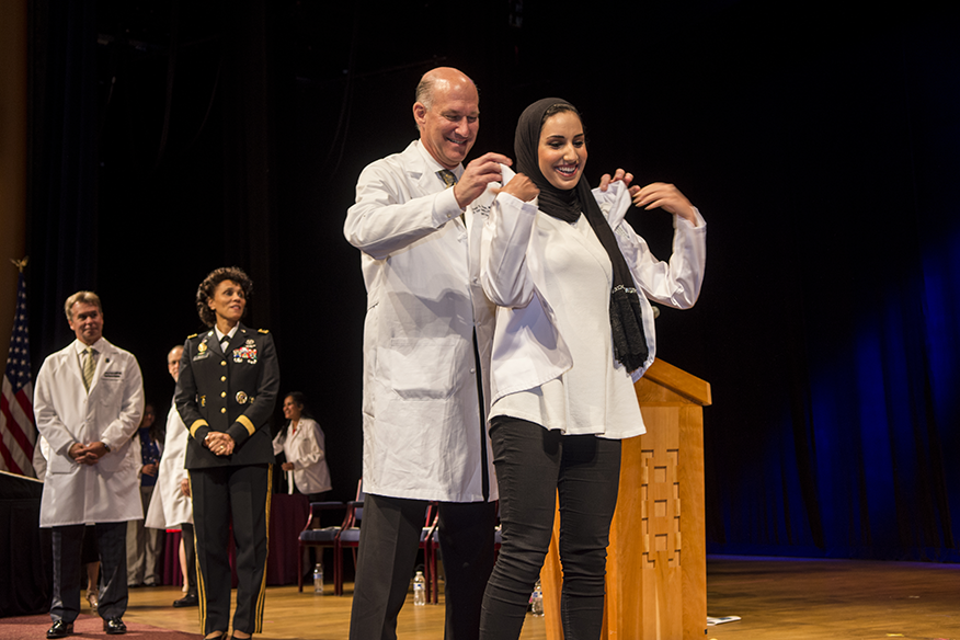 Jeffrey S. Akman, M.D. '81, RESD '85, helps a first-year M.D. program student put on her white coat.