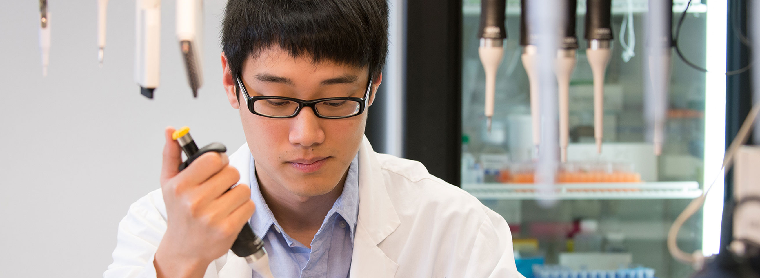 Research student in lab holding a piece of equipment