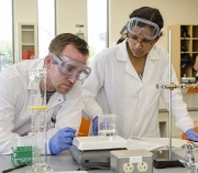 Students in white coats at a table weighing a beaker of liquid