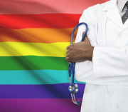 Doctor in front of a rainbow flag