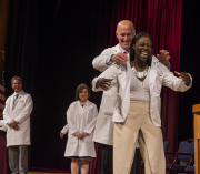 Jeffrey S. Akman, M.D., helps a first-year M.D. student formally don her white coat at the White Coat and Honor Code Ceremony on Aug. 6.