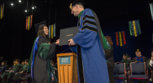 Dean Akman shakes hands with a graduating M.D. student