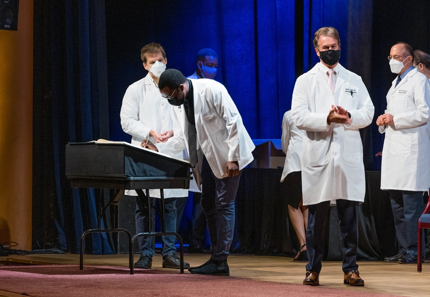 Student signing the honor code book at 2021 White Coat ceremony