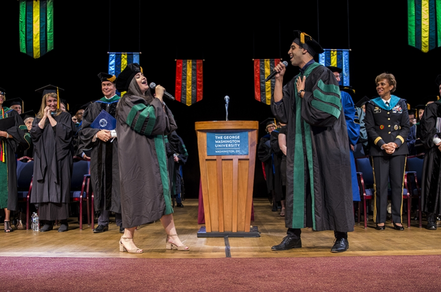 Two students singing onstage at graduation