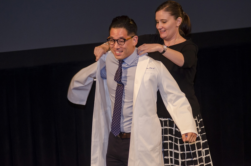 Professor putting white coat on student