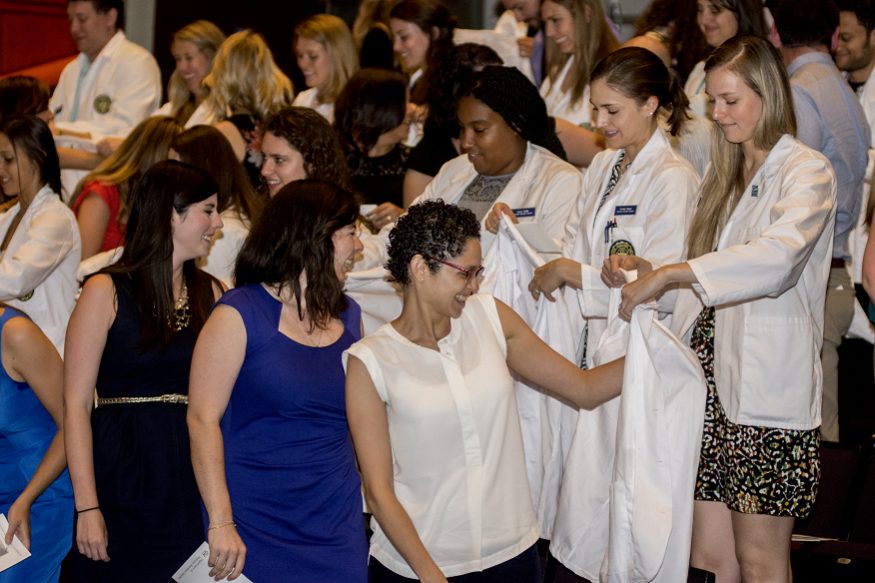 Second-year physician assistant (PA) students help first-year PA students don their white coats for the first time.