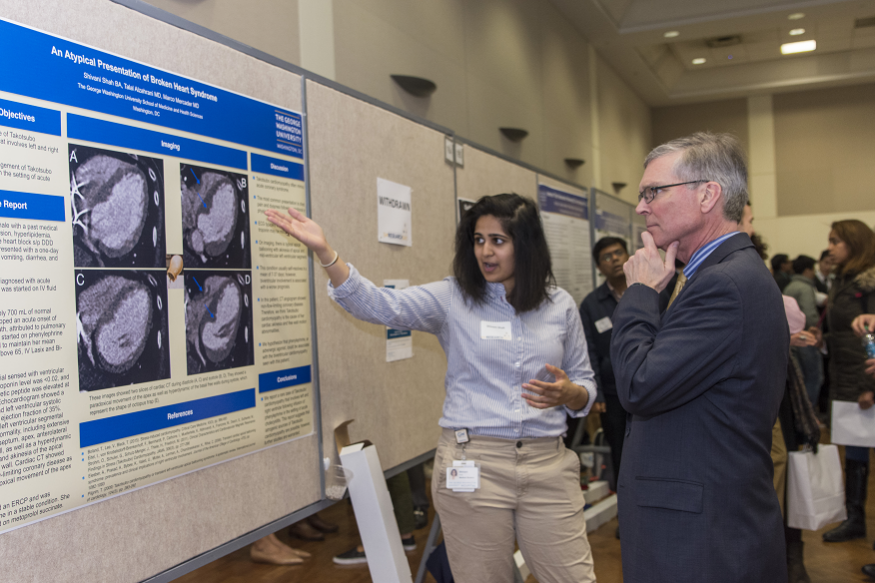 A student shows her poster to Scott Schroth, M.D.