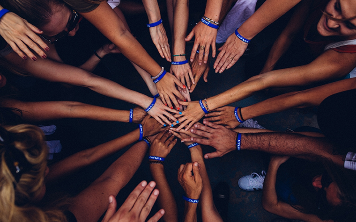 Hands of many volunteers in a circle