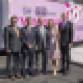 People stand in front of pink van