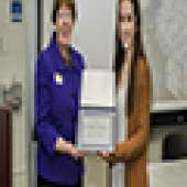 Two women standing holding plaque