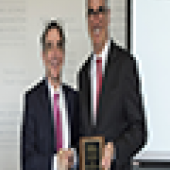 Two men standing at podium holding plaque