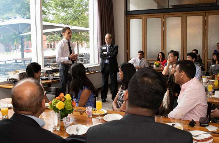 A MD student speaks to a crowd of people during a brunch at a restaurant