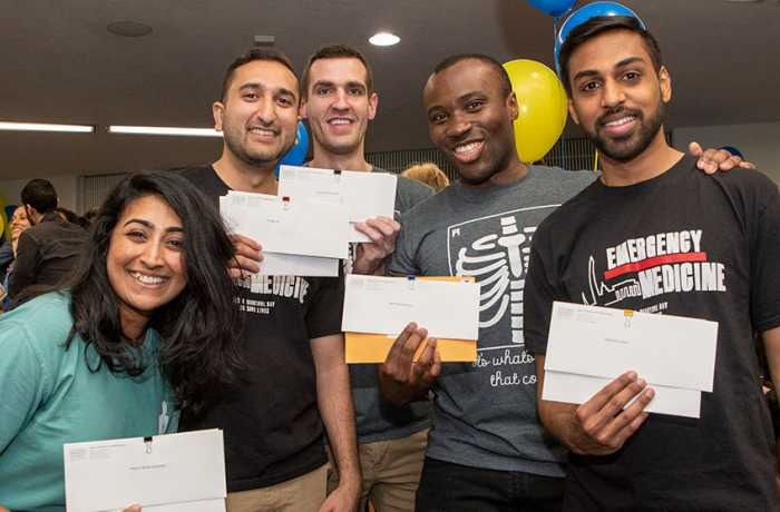 One woman and four men in T-shirts stand smiling holding white envelopes