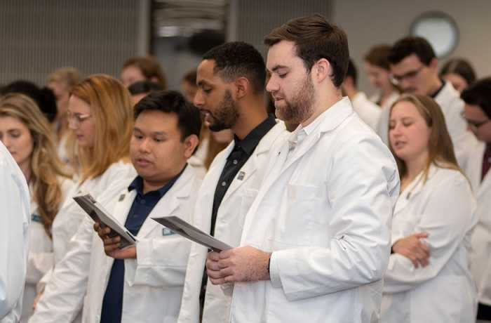 Students standing in white coats reading from paper program
