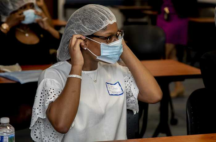 A participant in DC HEAL practices putting on scrubs.