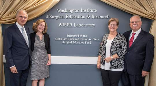 Colleagues stand in front of newly unveiled WISER laboratory sign