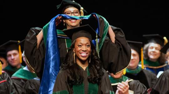 Graduate receives her hood on stage