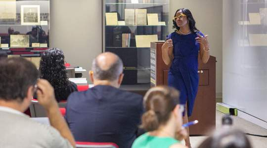 A woman talks to a group of faculty members