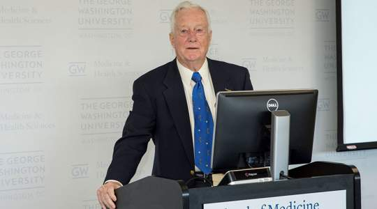 Man in blue ties stands in front of computer at podium
