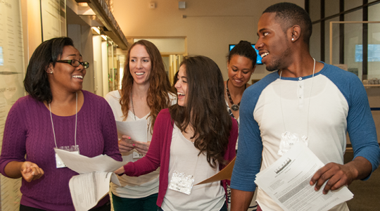 Student participants walk together through the Ross Hall lobby