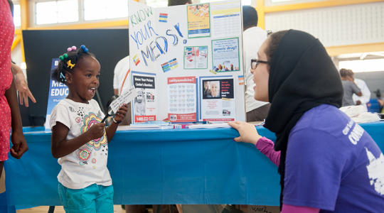 A Community Service Day volunteer interacts with a young participant.