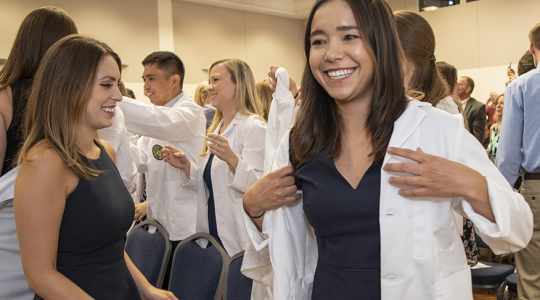 A new PA student dons her short white coat.