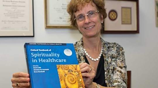 Dr. Puchalski holding Spirituality and Healthcare